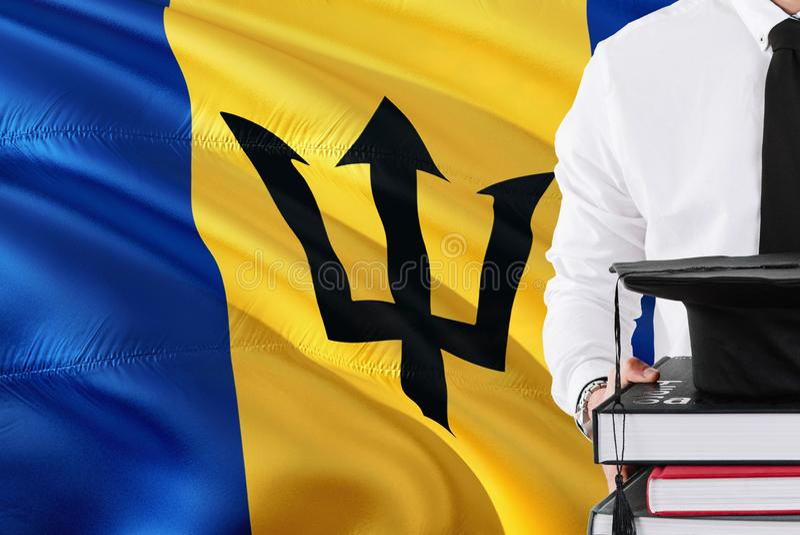 Het succesvolle concept Van Barbados van het studentenonderwijs Holdingsboeken en graduatie GLB over de vlagachtergrond van Barba stock afbeeldingen