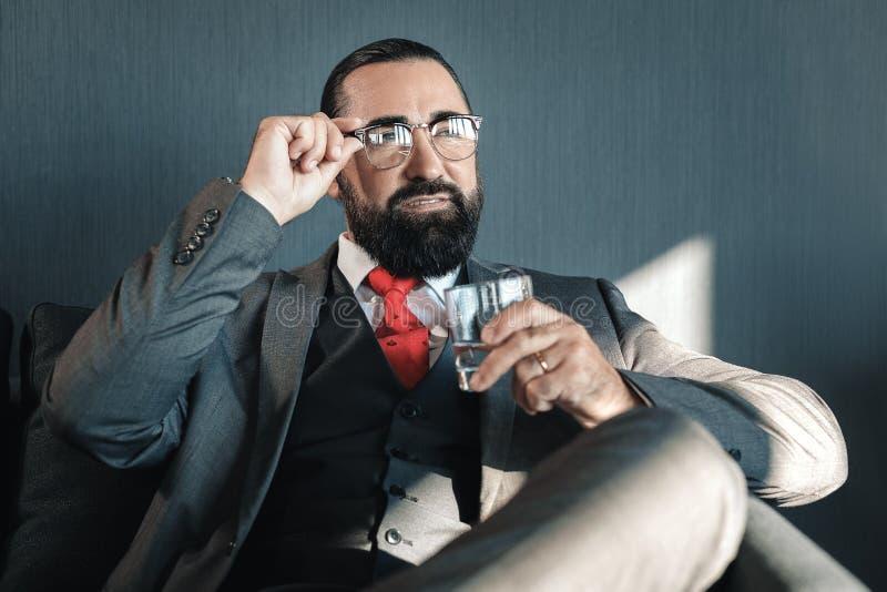 Het succesvolle glas van de zakenmanholding van waterzitting in hotelruimte royalty-vrije stock fotografie