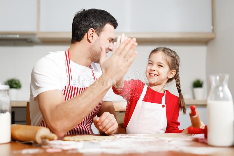 Het succesvolle kleine aanbiddelijke kind en haar hartelijke vader drukken hun instemming tussen elkaar uit, houden handen stock foto