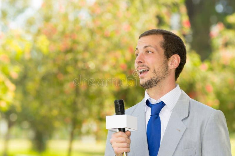 Het succesvolle knappe mannelijke nieuwsverslaggever dragen royalty-vrije stock afbeeldingen