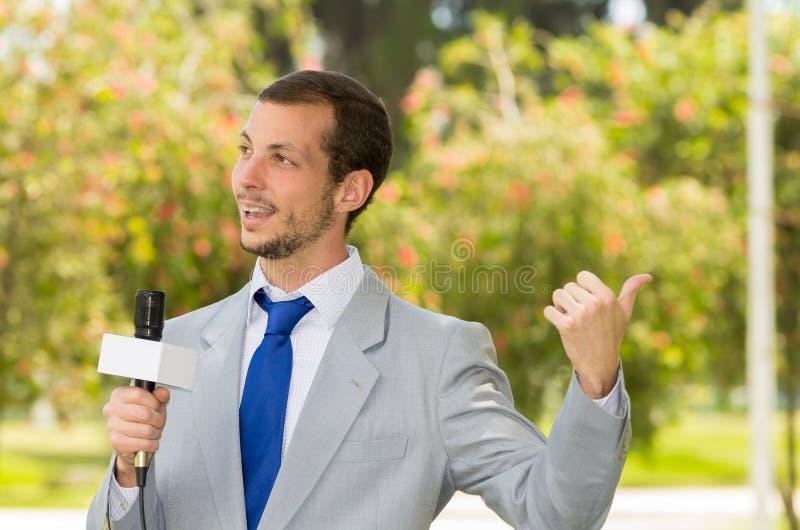 Het succesvolle knappe mannelijke nieuwsverslaggever dragen stock foto