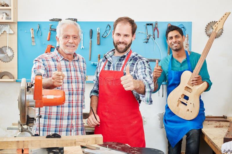 Het succesvolle luthiers houden beduimelt omhoog stock fotografie
