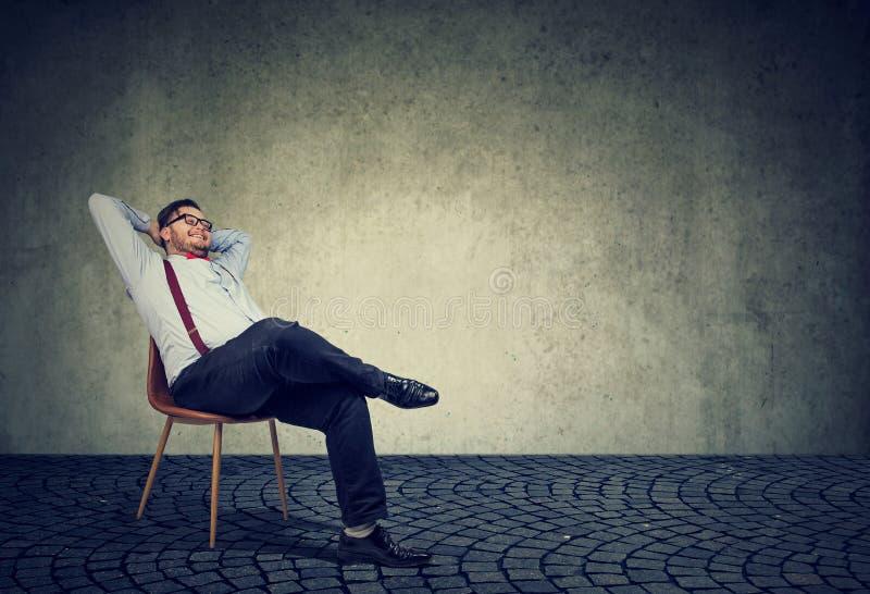 Het succesvolle mens ontspannen als voorzitter stock afbeeldingen