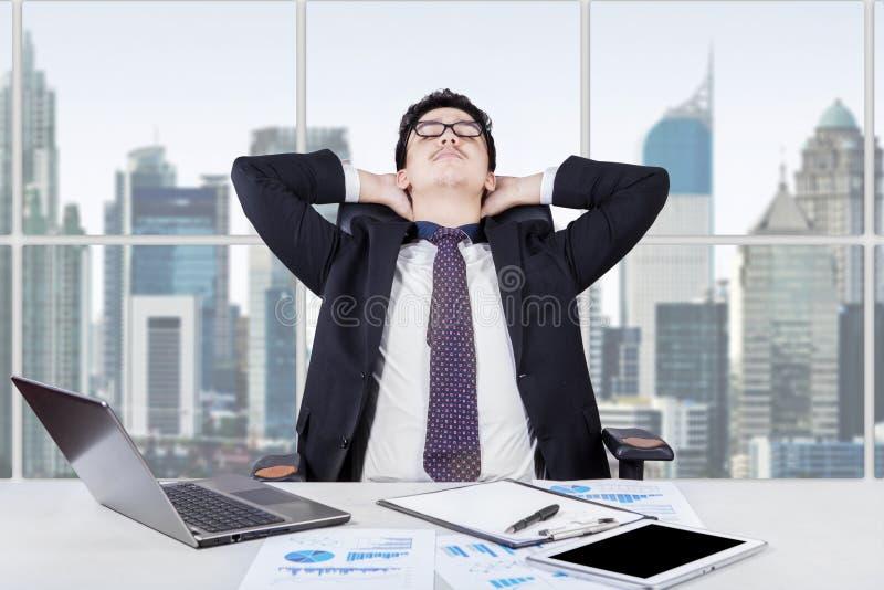Het succesvolle mens ontspannen in het bureau stock afbeelding