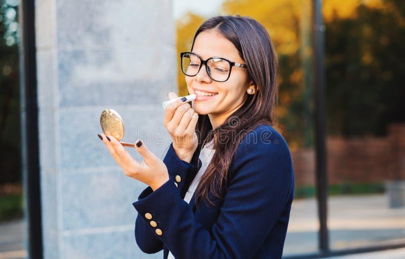 Het succesvolle mooie studentenvrouw kijken aan spiegel en verbetert haar make-up met lippenstift op de bureaubouw achtergrond stock afbeelding