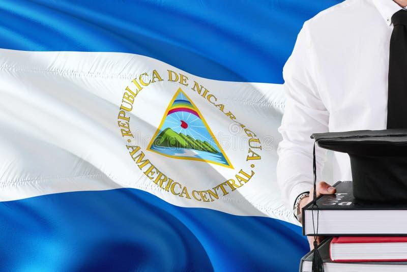 Het succesvolle Nicaraguan concept van het studentenonderwijs Holdingsboeken en graduatie GLB over de vlagachtergrond van Nicarag royalty-vrije stock foto's