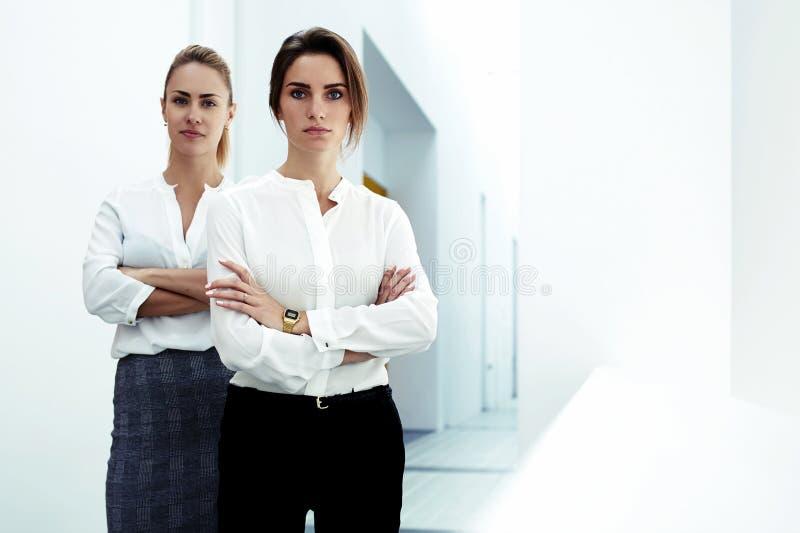 Het succesvolle team van jonge betrouwbare vrouwenleiders kleedde zich in het formele slijtage stellen samen in modern bureau, stock fotografie