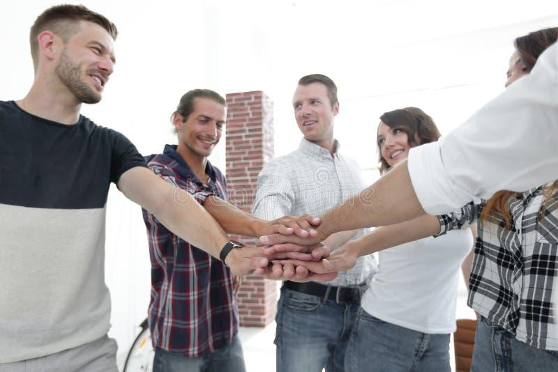 Het succesvolle team van ontwerpers clasped samen hun palmen stock afbeelding