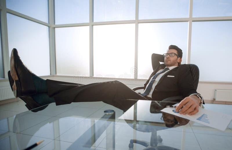 Het succesvolle zakenman ontspannen bij de lijst stock foto's