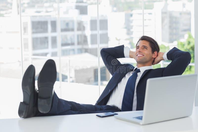 Het succesvolle zakenman ontspannen met zijn voeten op zijn bureau royalty-vrije stock foto's