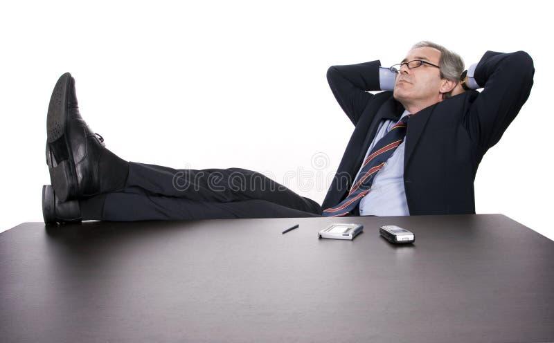 Het succesvolle zakenman ontspannen over zijn bureau stock afbeeldingen