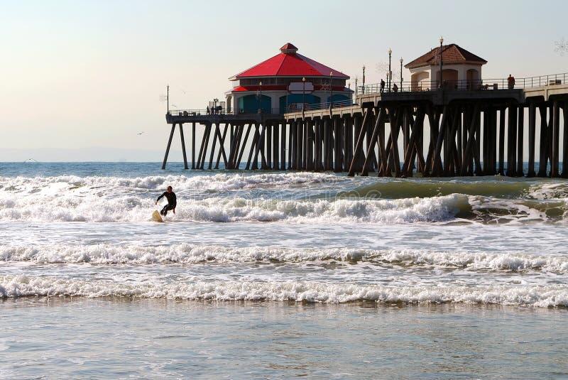 Het surfen door Pijler stock foto's