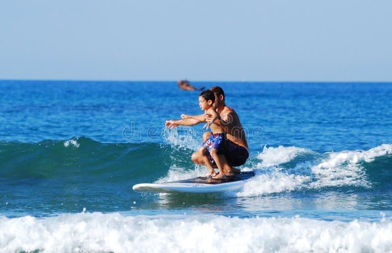 Het surfen met jonge geitjes stock foto's