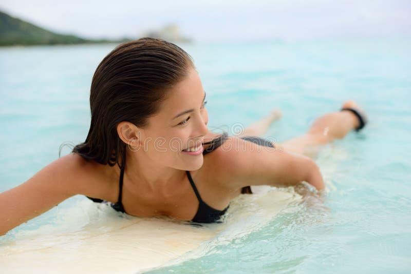 Het surfen van de peddel van het surfermeisje voor branding op surfplank royalty-vrije stock foto's