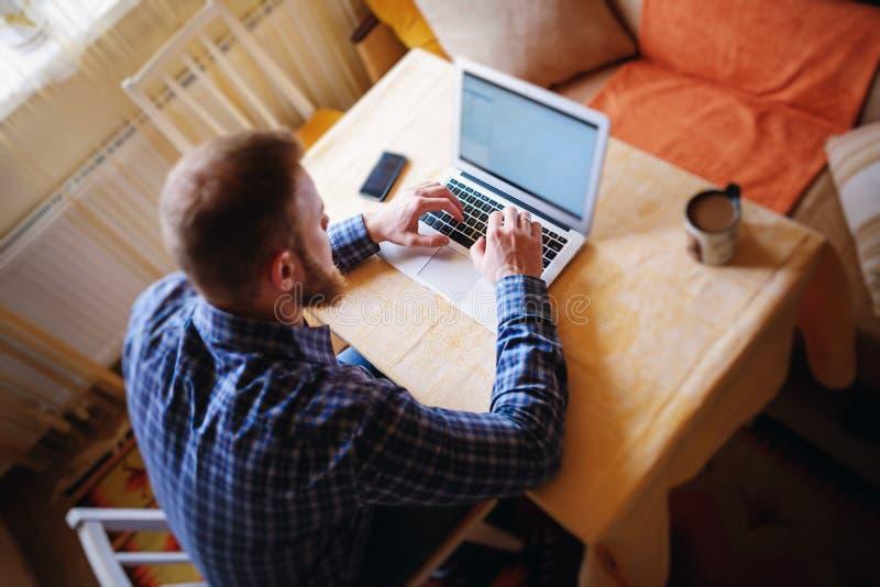 Het surfen van het net in bureau Zekere jonge aan laptop werken en mens die terwijl het zitten op zijn werkende plaats in bureau  stock afbeeldingen