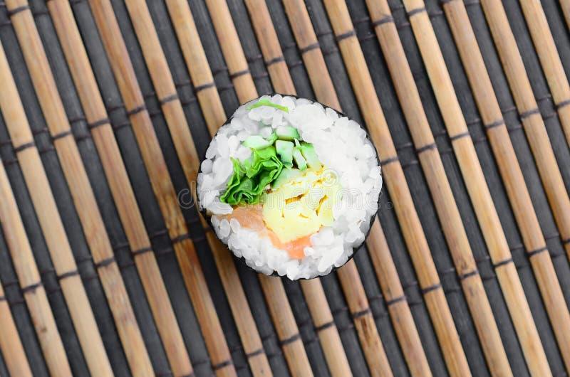 Het sushibroodje ligt op een serwing mat van het bamboestro Traditioneel Aziatisch voedsel Hoogste mening Vlak leg minimalism met royalty-vrije stock afbeelding