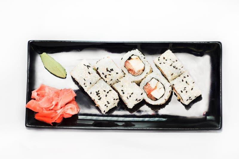 Het sushibroodje platted op een zwarte plaat royalty-vrije stock foto's