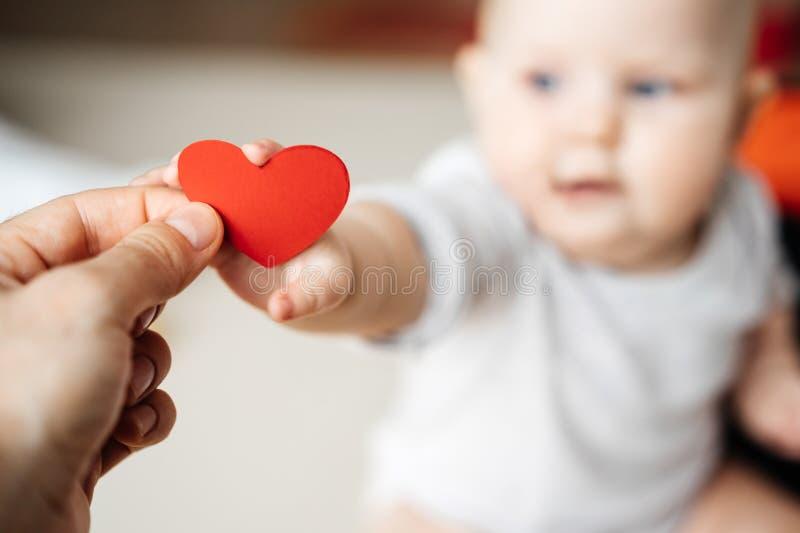 Het symbool van een rood hart in de hand van een mens die het overbrengen aan een kind in een kleine hand stock afbeelding