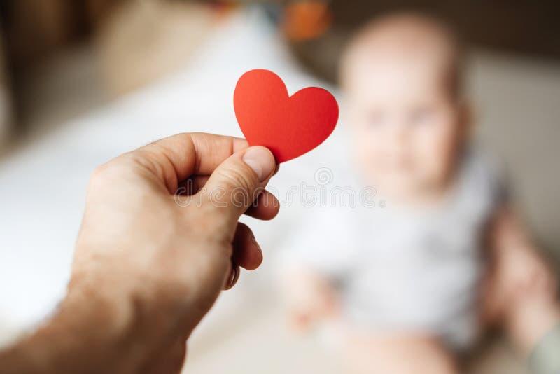 Het symbool van een rood hart in de hand van een mens die zijn kind geven stock foto's