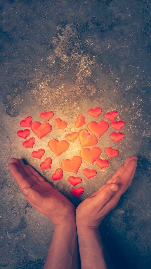 Het symbool van liefde en gezondheid is het hart in mannelijke handen Het brandende hart wordt opgemaakt van kleine harten in man stock fotografie