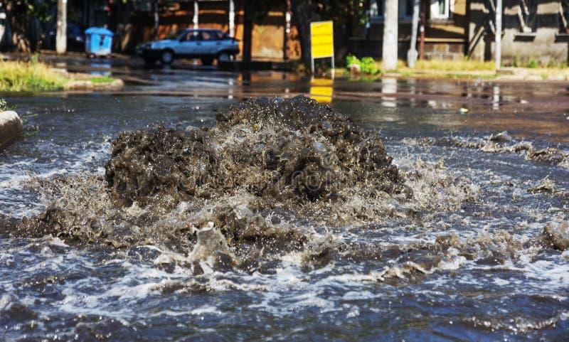 Het systeem van de ongevallenriolering Waterstromen over de weg van riool Ongeval in riool Het systeem van de doorbraakriolering  royalty-vrije stock fotografie