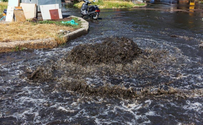 Het systeem van de ongevallenriolering Waterstromen over de weg van riool Ongeval in riool Het systeem van de doorbraakriolering  stock foto