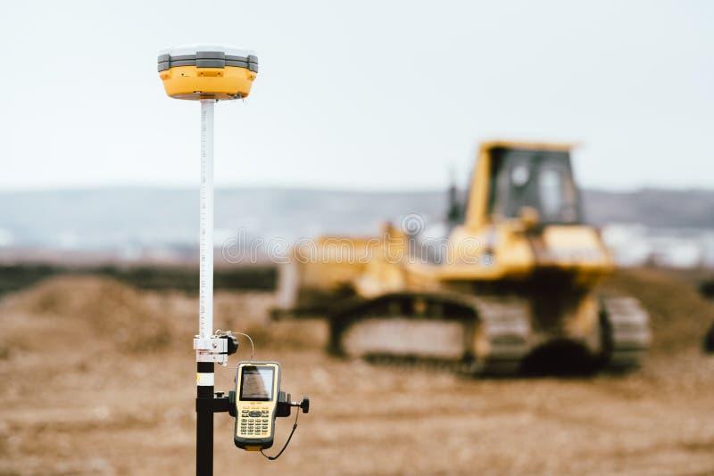 Het systeem van GPS van het landmetersmateriaal in openlucht bij wegbouwwerf Landmeterstechniek met het onderzoeken equipement stock foto's
