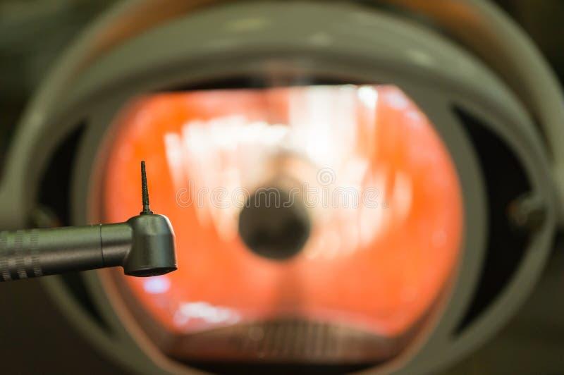 In het tandbureau - tandhandpiece en tanddienst-close-up tegen de achtergrond van een medische lamp Concept tand stock foto