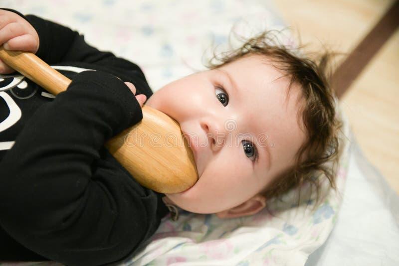 Het tandjes krijgen in een kind tandenjeuk knaagt aan een lepel Mijn gommen jeuken, ga ik sommige tanden spoedig worden stock foto's
