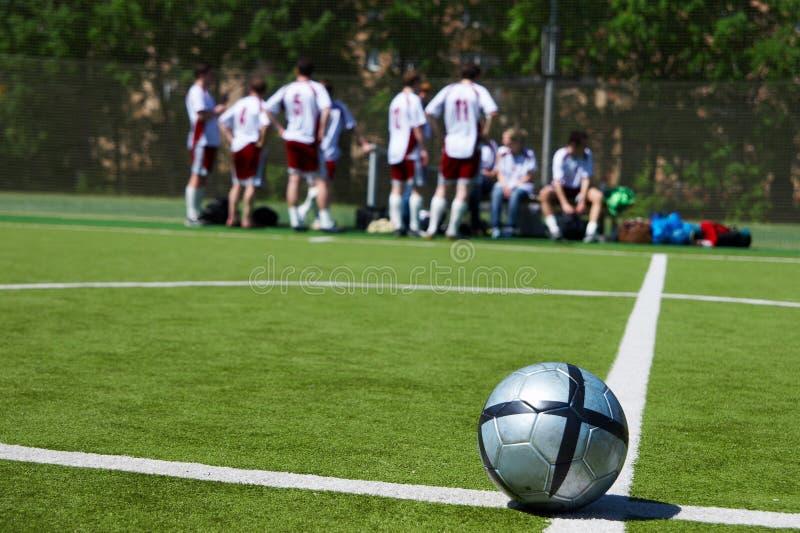Het team dat van het voetbal op achtergrond rust royalty-vrije stock fotografie