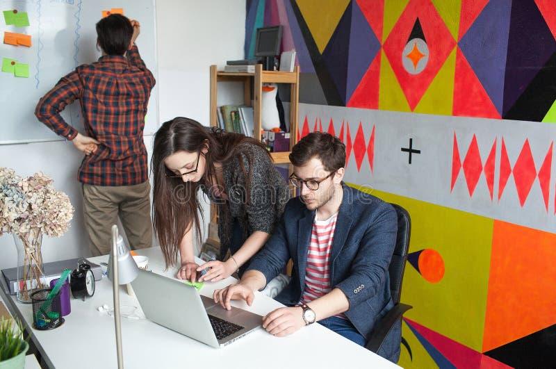 Het team die van Yong hipster in modern bureau werken stock afbeeldingen