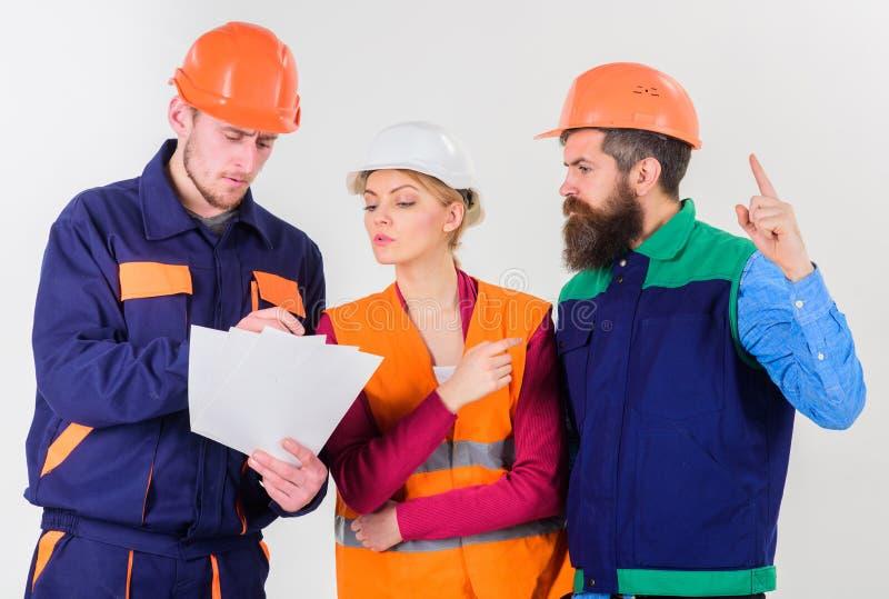 Het team van architecten, ingenieurs bespreekt, bekijkt document, stock afbeeldingen