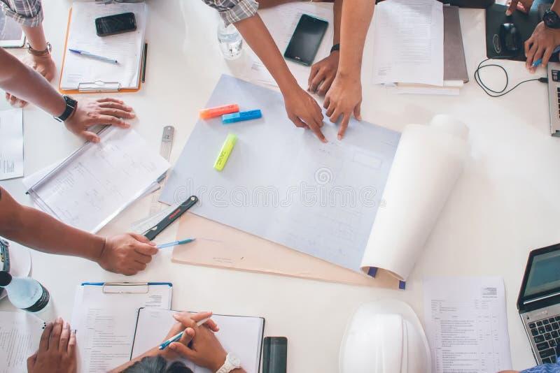 Het team van architectenmensen in groep op construcitonplaats controleert documentenwerkschema stock afbeelding