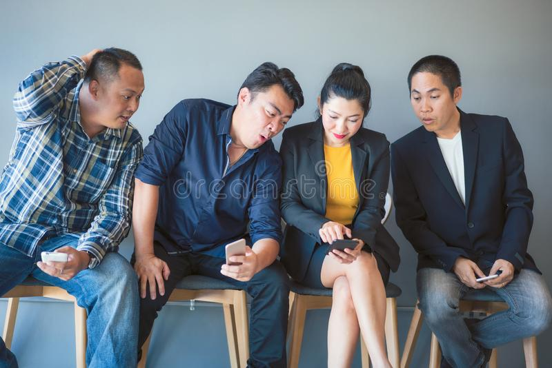 Het team van bedrijfs Aziatische mensen is opgewekt over de informatie over smartphone van de groepsleden terwijl het wachten op  royalty-vrije stock afbeeldingen