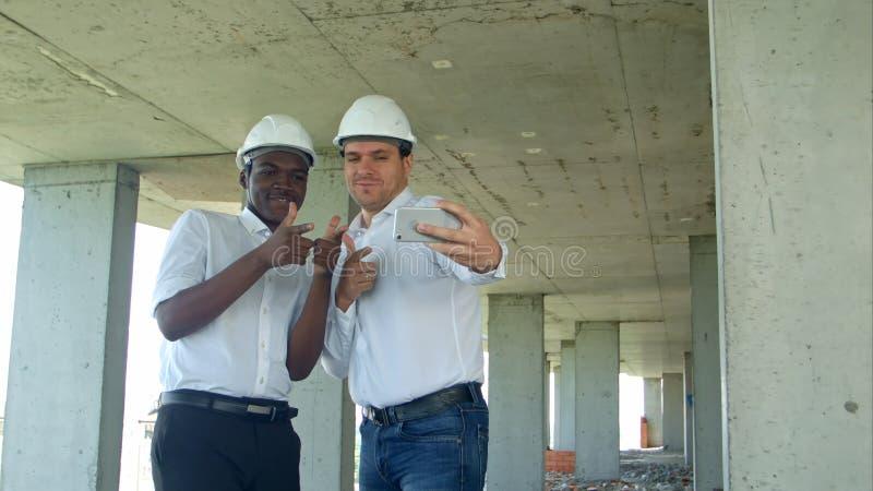 Het team van bouwers het gelukkige glimlachen neemt selfie foto tijdens vergadering over bouwwerf royalty-vrije stock afbeelding