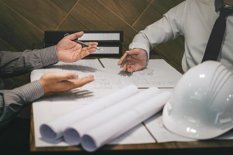 Het team van constructiewerkzaamheden of de architectenpartner bespreekt een blauwdruk terwijl het controleren van informatie bij stock afbeeldingen