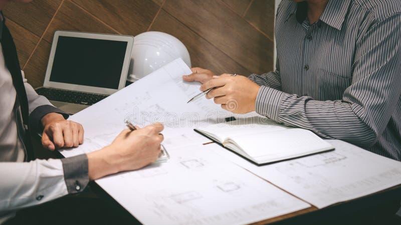 Het team van constructiewerkzaamheden of de architectenpartner bespreekt een blauwdruk terwijl het controleren van informatie bij royalty-vrije stock foto