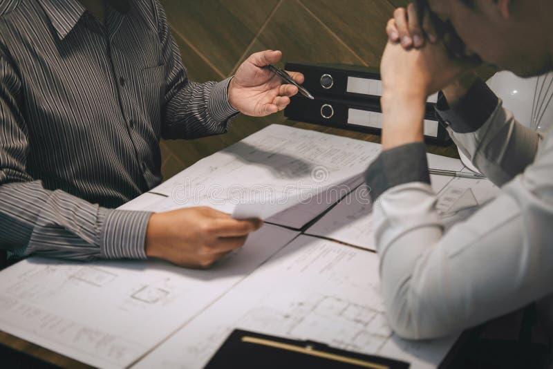 Het team van constructiewerkzaamheden of de architectenpartner bespreekt een blauwdruk terwijl het controleren van informatie bij royalty-vrije stock foto's