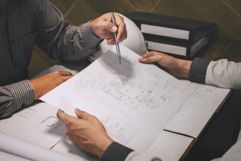 Het team van constructiewerkzaamheden of de architectenpartner bespreekt een blauwdruk terwijl het controleren van informatie bij stock foto's