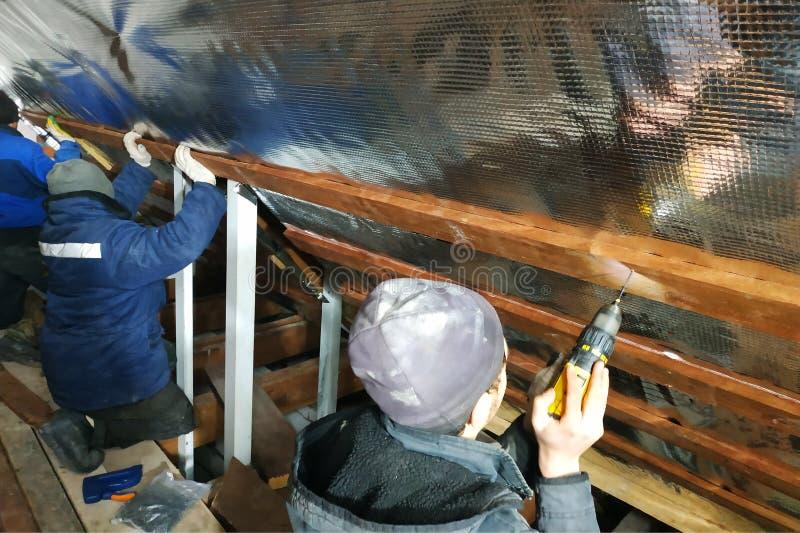 Het team van de meesters installeert het dak van het huis, en schroeft in het bijzonder de schroeven in de raad voor het bevestig royalty-vrije stock foto