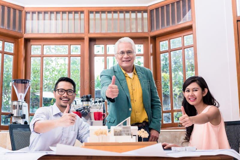 Het team van drie het succesvolle architecten tonen beduimelt omhoog royalty-vrije stock afbeeldingen