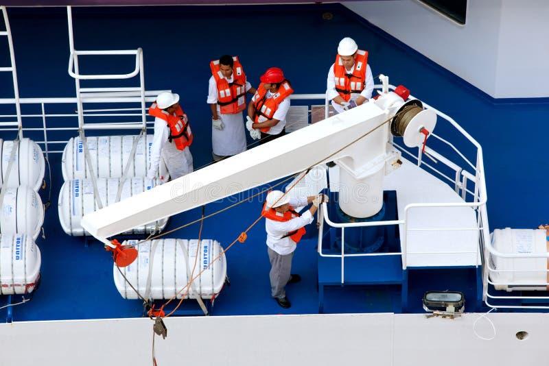 Het team van het personeel met reddingsvesten bij redding de opleiding stock afbeelding