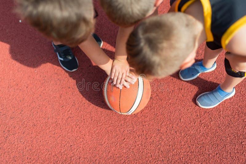 Het Team van het jonge geitjesbasketbal Jonge de Holdingsballen van Basketbalspelers op Basketbalhof stock afbeeldingen