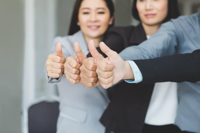 Het team van zaken sluit zich aan bij krachten die en duimen uitwerken tonen als Si stock afbeelding