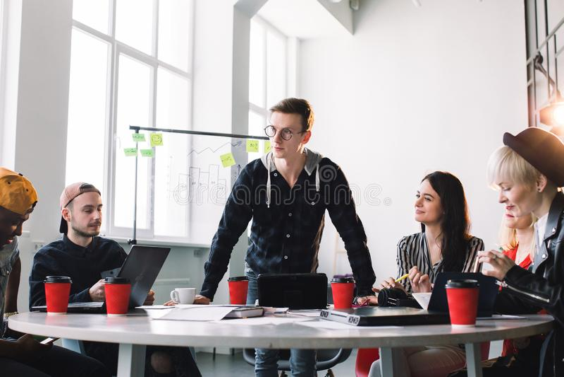 Het teamwerk en de teambouw zijn een succes Bezige startpartners die in vrijetijdskleding werken, die de leider luisteren royalty-vrije stock fotografie