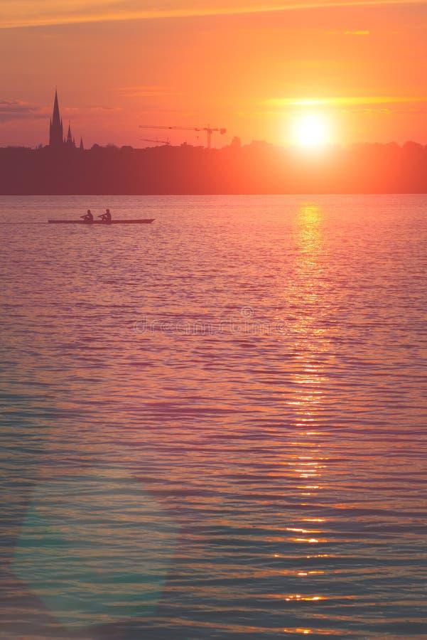 Het teamwerk van jonge die mensen op een rij boot bij zonsondergang wordt gesilhouetteerd Mooie grote zon lichte gloed stock afbeelding