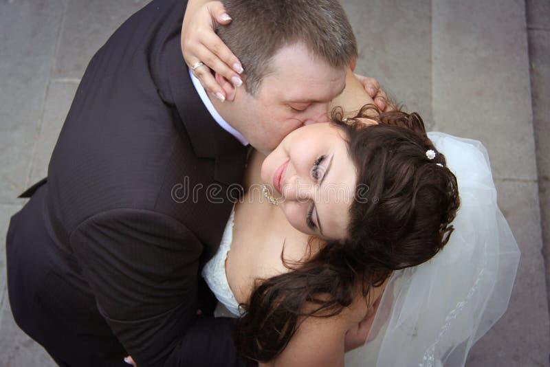 Het tedere kussen van jonggehuwden stock afbeelding