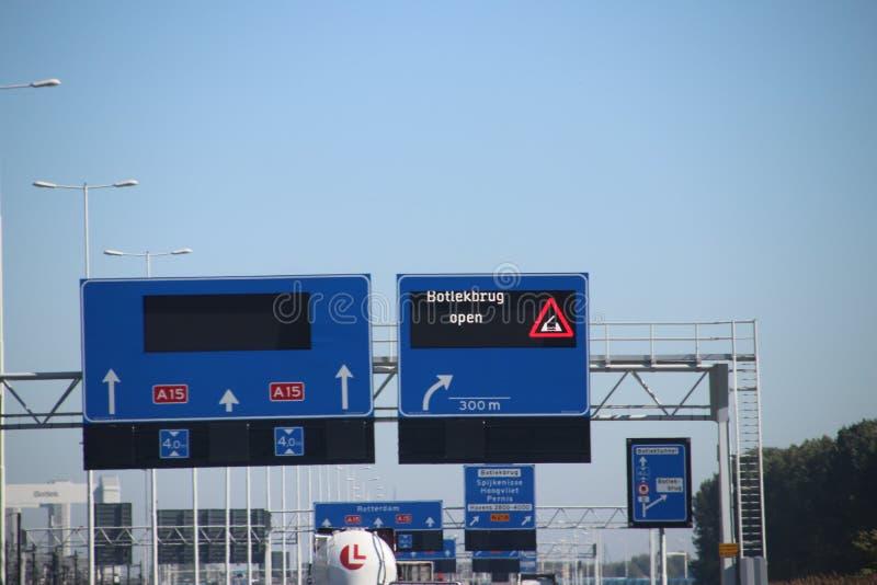 Het teken boven de weg met waarschuwing dat de brug Botlekbrug noemde is open wat invloed van gevaarlijk goederenverkeer hebben royalty-vrije stock foto