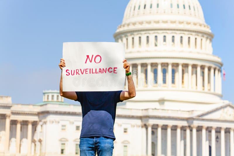 Het teken die van de protesteerderholding geen toezicht verbergend gezicht zeggen stock afbeeldingen