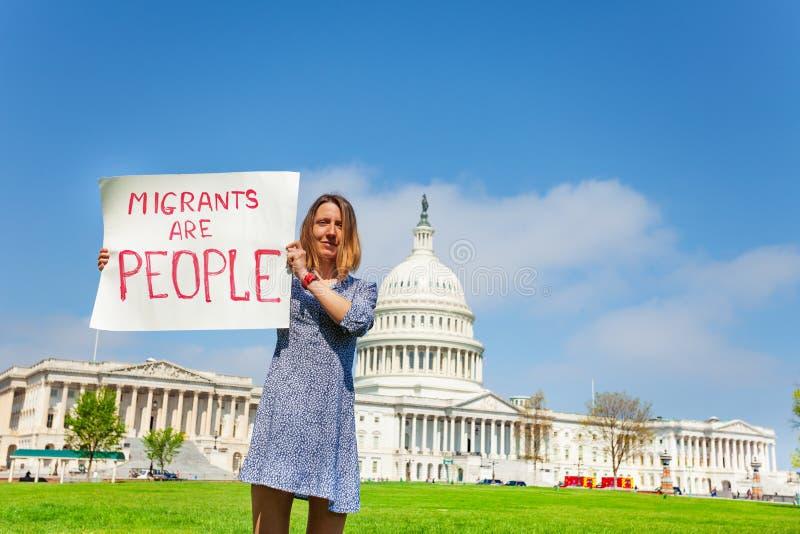 Het teken die van de protesteerderholding migranten zeggen is mensen stock foto